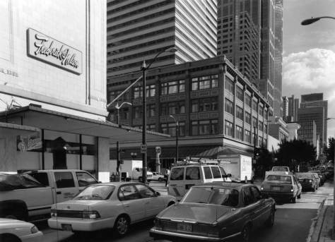 "With the last reprinting of Seattle Now & Then Volume 1, I returned to many of the subjects and updated their ""repeats"" including this look south down 5th Avenue into its intersection with Pine Street.  Frederick and Nelson Dept. Store was still in place, although barely."