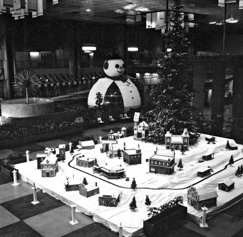 "From the balcony at the Food Circus/Centerhouse, Frank Shaw looks over the oversized winter model train set to the old Century 21 ""Bubbleator"" dressed as a snowman.  Shaw took this two days after Christmas, 1976, when the place is resting."