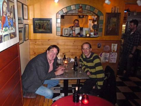 """Except for what remains of the wine the Swingside table has been cleared.  Jean and Steve pose below the kitchen window where Swingside owner-shef Brad appears half-bent over his """"stove."""""""