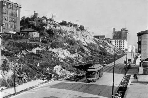 The Blanchard Apartments are still in place, upper-left, although the Second Avenue Regrade (an early part of the Denny Hill Regrade) has been completed.  In the distance are both the white Moore Theatre at Virginia and the New Washington Hotel at Stewart.  The original photograph was recorded by the Webster Stevens studio and is used here courtesy of MOHAI.