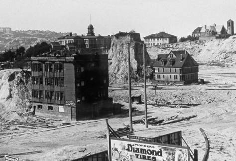 This view and the one below it look from some surviving structure on the west side of Second Avenue to the northeast and so cut diagonally across both Second Avenue and Blanchard Street.  The horizon includes the new (1909) Ballard High School on the left, and Denny School, the tower above the Blanchard Hotel and left of the surviving spike.  He big residence - probably a boarding house - just south of the spike was skidded there from a location about one block to the east.   Sacred Heart Parish is on the right horizon.   Both Denny School and Sacred Heart survived there until the regrade picked up again in 1928 at the cliff it left to stand for 18 years along the east side of 5th Avenue after the regrading reached it in 1911 and then temporarily stopped  .