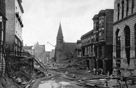 The Third Ave Regrade in 1907.  A partially razed Washington Hotel is on the horizon, and Plymouth Church escapes it.  The two-gables structure is on the rigth and to this side a new structure with a tiled front, which would suvive until the city's modern preparations for Century 21.