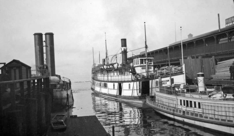The twin-stacked Duwamish again in its slip between Pier 3(54) on the right and Grand Trunk Dock. Here the steamer Reliance has taken the place of the Inland Flyer. The fleet little vessel on the far right does not show her name. This view also came with a collection of mostly Seattle waterfront prints from a historical association in north Idaho. It now resides in the University of Washinton's Special Collections.