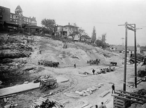 "Regrade work on Pine Street looking northeast into the front ""hump"" of Denny Hill with the hotel still on top.  Note the tower for the fire station far right."
