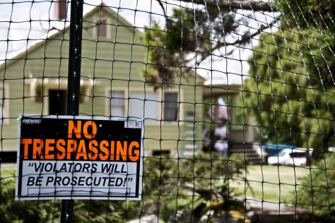 """The black plastic fence was liberally covered with 'No Trespassing' signs, warning off the peaceful crowd, lest they attempt to """"storm the property"""". A couple of sheriffs' squad cars were also present."""