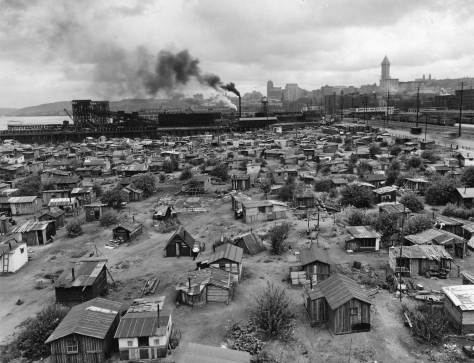"This is most likely the most oft-published panorama of Seattle's own Hooverville, photographed here from the roof of the B.F. Goodrich Rubber Company building at the southwest corner of what were then Connecticut Street and Railroad Avenue and are today Royal Brougham and East Marginal Ways.  Here we see a little more than half of the 500 shanties that live-in sociologist Donald Francis Roy described as ""scattered over the terrain in insane disorder . . . in this labyrinth the investigator wandered for days, pacing off length and widths and distances fomr this to that and achieve, after a great sacrifice of leather, a fairly accurate map."