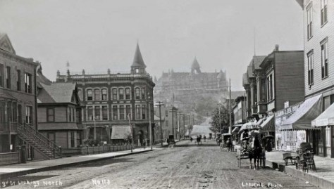 Looking north on 3rd Ave. with his back near University Street, LaRoche captures on center horizon the looming haze-shrouded mass of the Denny Hill in the early 1890s