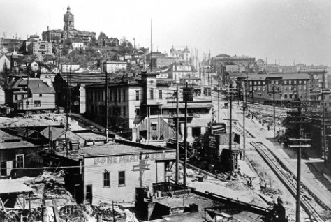 "With the cables open for repair running on the right up Yesler Way, this classic reveals a line-up of civic landmarks beginning with the King County Courthouse on the horizon of ""Profanity Hill.""  The sprawling clapboards at the subject's center is the still celebrated Katzenjammer Kastle, City Hall following the Great Fire of 1889 for nearly 10 years.  City Light's transfer station can also be found, and closes to the photographer if Bohemian Beer, a brand I'm familiar with in that Herman Keys, my painting instructor and friend in Spokane, married into the family and thereby operated a salon for a circle of friends in the Bohemian Manse with its upper class footprint firmly planted in Spokane's oldest distinguished neighborhood, the Brown's Addition west of the business district."