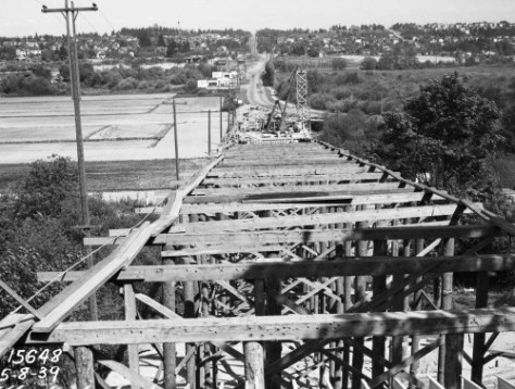 """Construction of the 45th Street Viaduct between the """"upper"""" University District and the U.W. Campus and the many plant nurseries fated for the development of University Village.  The Municipal Archive subject dates from 1939 and so too early to find in the distance any traced yet of the Union Bay Village, although its triangle has been cleared, top-right."""