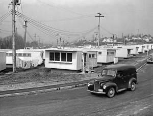 """THEN: On March 25, 1946, or near it, Wide World Photos recorded here what they titled """"University Vet Housing."""" It would soon be named the Union Bay Village and house the families of returning veterans. The first 45 bungalows shown here rented for from $35 to $45 dollars a month. It would increase to a """"teeming conglomerate of 500 rental units."""" With housing for both married students and faculty. The view looks north over a street that no longer exists. The homes on the right horizon face the Burke Gilman Recreation Trail on N.E. Blakeley Street near N.E. 45th Place. (Courtesy Ron Edge)"""