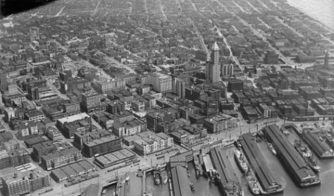 "Looking east over much of the business district in an aerial (and damaged print) from 1929.  The reader is encouraged to try some hide-and-seek when comparing with oblique aerial with the vertical ""map aerial"" that follows covering much of the same neighborhood."