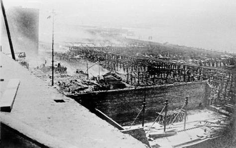 "A sidewalk view revealing the savior-wall at the base of the south facade following the June 6, 1889 ""Great Fire"" that consumed most of the Seattle waterfront - to the tides - and over 30 city blocks. The view looks south-southwest.  The north facade of the ruined cracker factor at Seneca is seen in part at the top-left corner."
