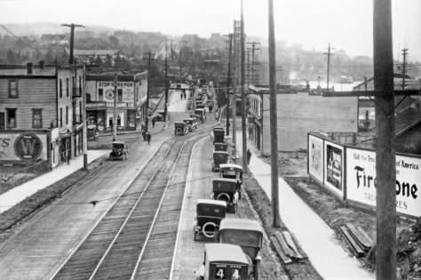 THEN: The historical view looks directly south into the Latona addition's business district on Sixth Ave. NE. from the Northern Pacific's railroad bridge, now part of the Burke Gilman Recreation Trail. (Courtesy, Lawton Gowey)