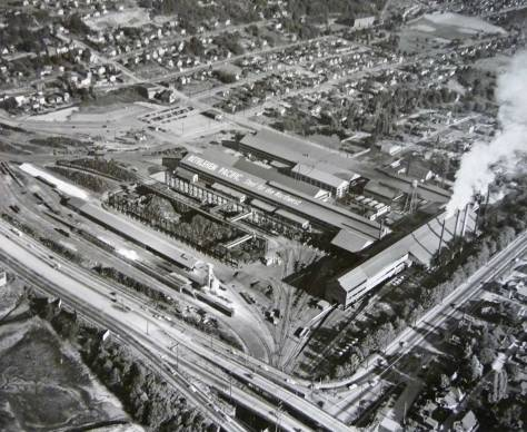 "Another aerial of Bethlehem Steel, this one looking to the southeast with Spokane Street on the left. It is dated tentatively ca. 1955.  Avalon Way is bottom right, and the climb on Andover east up to Pigeon Point is upper-left.  The building on the right, with the five mostly smoking stacks, housed the open hearth furnaces where scrap steel was transformed into ""new old steel.""  Soon after this aerial was recorded the plant would be closed for installation of electric steel making equipment, in 1958.  [Courtesy, MOHAI]"
