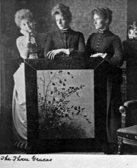 album-[The-Three-Graces]-3-women-stand-over-painting-interiror,-maslanWEB
