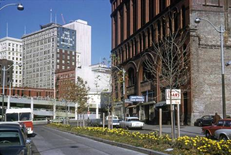 This time Lawton returns on November 11, 1972 for the nearly new planter strip centered on Occidental Avenue.  Jesus and the bar endure, joined now by another kind of savior,