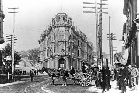 The Occidental Hotel from the front.  James Street is on the left, and Mill Street (Yesler Way) on the right.  In the foreground, Commercial Street (First Ave. South) originates out of Mill Street.