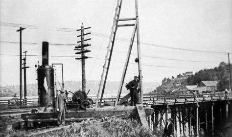 The Fremont low bridge (one of them) from its north side.  The use of the pile driver in the foreground is not explained.  The date on this one is.  It is April, 1907, and the same day that the featured photo (at the top) was recorded.