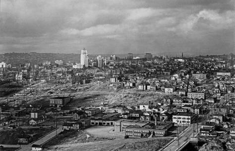 THEN: This Seattle Housing Authority photograph was recorded from the top of the Marine Hospital (now Pacific Tower) on the north head of Beacon Hill. It looks north to First Hill during the Authority's clearing of its southern slope for the building of the Yesler Terrace Public Housing. (Courtesy, Lawton Gowey)
