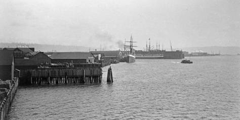 Another early post-fire Haynes view of the waterfront, this one most likely from the Madison Street coal wharf.  The competing King Street coal wharf and bunkers reaches into the bay at the scene's center.   Yesler's post-fire wharf is marked left-of-center.  (Courtesy, Tacoma Public Library)