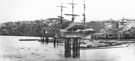 Photographed by Morford from Yesler's Wharf in late 1887 or 1888.  Madison Street lumber-bound wharf is on the far right, Denny Hill behind the tall ship.