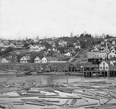 "A Peterson and Bros. photograph taken from the end of a dog-legged Yesler Wharf and looking up Columbia Street on the right in 1878.  Note the tower for the ""White Church"" on the right, the Methodist Episcopalian congregation that was the first in Seattle.  It sits there at the second lot south of Columbia on the east side of Second Avenue.  Also note that for the most part First Hill has been denuded of the virgin forest that still covered this skyline as late as 1872."