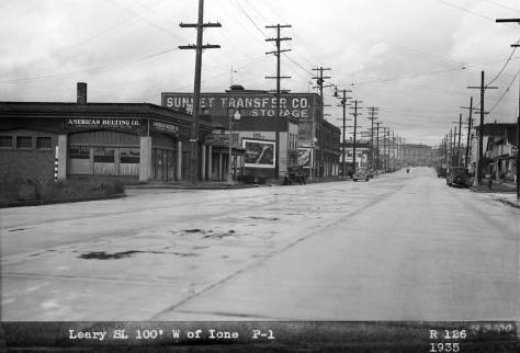 """Looking northwest on Leary Way to its intersection with Ione Place.  The caption makes not of its billboard subject as """"100 feet west of Ione."""""""
