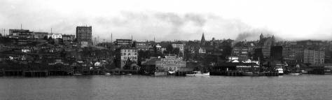 The waterfront at the foot of Pike Street photographed from bay shows the Hotel York on the left horizon.