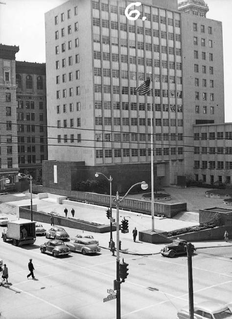 "The Public Safety Building took the block in 1951, one of downtown Seattle's earliest Modern Building. Here looking southwest thru the intersection of Fourth Ave. and Cherry Street, the City County building looks back, on the left, and the Smith Tower peeks over, upper-right.  The number ""6."" scrawled on the photo is not explained.  (Courtesy, Seattle Municipal Archive.)"