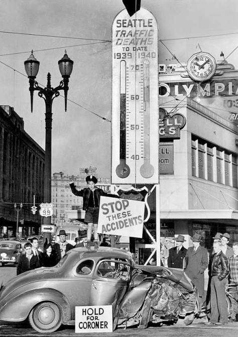 """THE SEATTLE TIMES caption for the above reads, """"Grim reminder of what might happen to reckless and drunken drivers in heavy traffic tonight, the above wrecked automobile, involved in a recent collision, was parked today at the base of the death termometer which has beenused by the seattle Traffic and Safety Council to record the city's traffic toll.  The thermometer is at Fourth an dWetlake Avenues. Perched atop the car is """"Safety Pete,"""" official mascot of the Safety Council."""""""