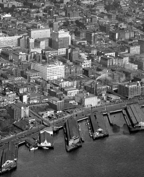 "A mid-20's aerial that is ""bordered"" by two viaducts, the one between the Pike Place Market and the Pike Street Pier, on the left, and, on the right, the still standing timber trestle between First Ave. and the Waterfront, on the right."