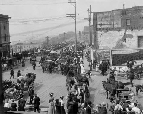 This 1907 look north up Pike Place must be considered the market classic.  The stalls are yet to be built, so most of the commerce is done from the farmer's wagons.  The Hotel York, victim of the railroad tunnel below it, has left a hole on the right - behind the billboards.  (Courtesy, Oregon Historical Society)