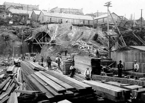 Work at the north portal, ca. 1903-4.  The tunnel workers' dormitories are lined up above the opening.  Later the Municipal Market Building would nestle on that ledge.