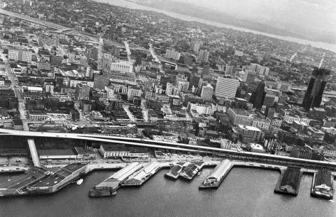 The Muncipal Market Building can be found here just above the Alaskan Way Viaduct and left-of-center.  A few cars are parked on the roof.  Work on the First National Bank building, far-right, is approaching its topping off, ca. 1967-8.