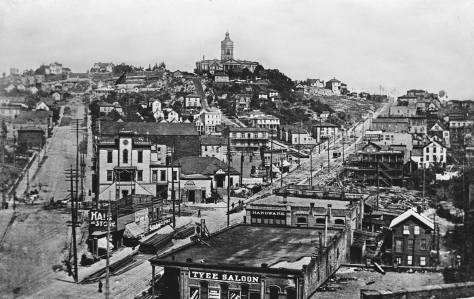 "The first brick home is found in this look up First Hill below the towered Court House on the horizon. That is Terrace Street with the steep steps climbing to the top of ""Profanity Hill.' Jefferson Street is on the left and Yesler Way cuts through the cityscape. City Hall is left of center, the bright facade with the centered tower. It faces Third Avenue."
