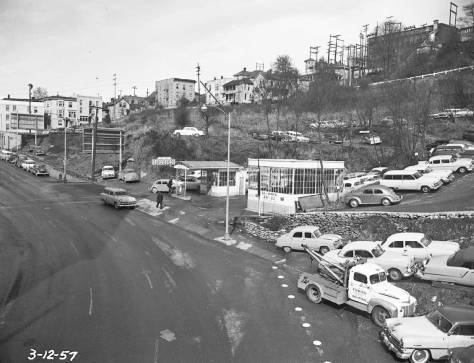 March 12, 1957, looking north on Fifth Avenue from the Yesler Way overpass into part of the sprawling and steep parking lot developed on the shaky acres once home to the tenements on Fifth Avenue's east side. Courtesy, Seattle Municipal Archive.