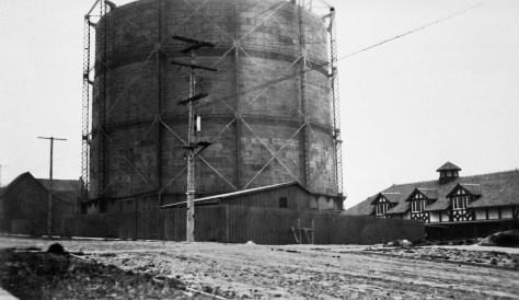 THEN: This portrait of the Seattle Gas Company's storage tank dates from the spring of 1907, which explains its somewhat steeper topography. Between 1908 and 1911, both Republican Street, here on the right, and 9th Avenue N. were lowered to a grade close to that of Westlake Avenue, which is behind the photographer.