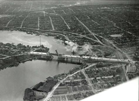 Pilot-photographer Laidlaw's Arpil 17, 1933 aerial of the completed approaches to the University Bridge, with the temporary bridge still in place to this (east) side of it. The photo is dated April 19, 1933, two weeks following the new 6-lane bridge's dedication. [Courtesy, MUSEUM of HISTORY and INDUSTRY aka MOHAI]