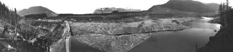 A pan of the dam, its reservoir and surrounds to the east, north and west. Partly cut-off on the right is Mt.Washington. Mt. Si is at the center horizon, and Rattlesnake Mountain or ridge is on the right, to the west. I do not have a date for this, but I suspect that it is during the late construction on the dam and so before t he leaking.