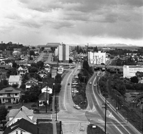 "A circa 1961 look east from the nearly completed work on the Freeway Bridge down on ""our"" odd corner of 7th Ave. NE and NE 40th Street - at the bottom. The still mostly barren Campus Parkway appears upper right, the Applied Physics Laboratory, right-of-center, and one of the rail spurs off the still tracked SLSERR bed is still intact on the far right, with Mt. Si on the horizon."