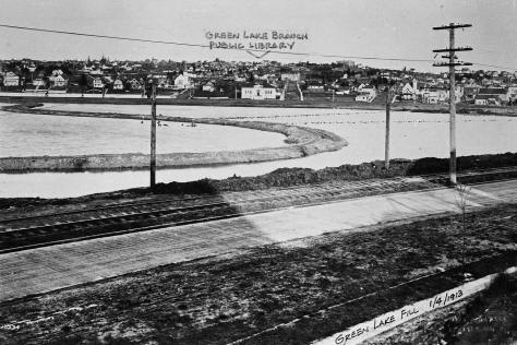 The snaking dirt platform for supporting the narrow-gauged railroad used to fill in the bay. Note both the new Green Lake Library and Bethany Lutheran Church, one block to the left of the library.