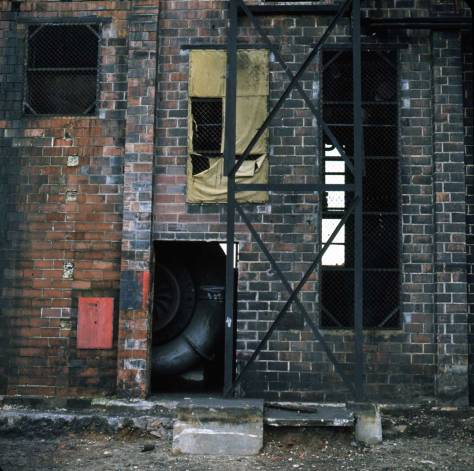 """Brick building under cracking tower, Feb 7, 1974."""