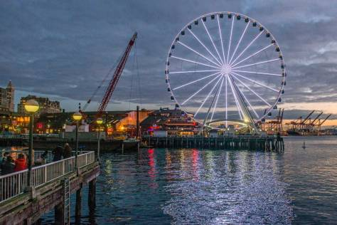 NOW: Jean Sherrard also looks south, but from the Pike Street Wharf, and across the open water of Seattle's Waterfront Park and a twilight that reaches from the container cranes on Harbor Island, on the right, to the Smith Tower on the left.