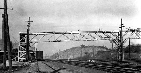 The pedestrian trestle still under construction, looking north along the tracks. (Courtesy, Seattle Municipal Archive)