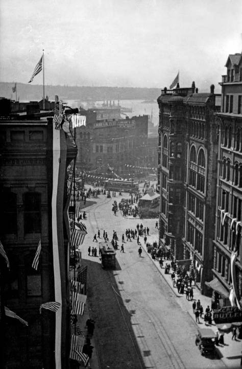 Looking west on James St. from the Collins Building at its southeast corner with Second Avenue. Some of the Fleet-visit bunting can be seen here draping a corner of the Seattle Hotel.