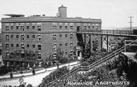THEN: Built in 1909-10 on one of First Hill's steepest slopes, the dark brick Normandie Apartments' three wings, when seen from the sky, resemble a bird in flight. (Lawton Gowey)