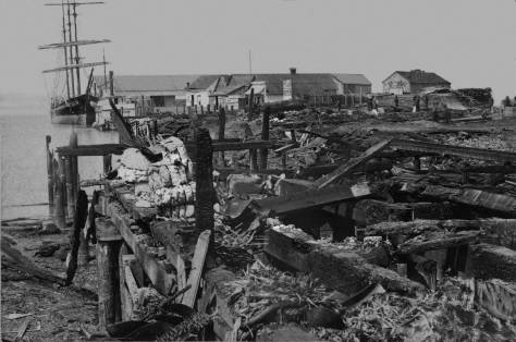 THEN:Ruins from the fire of July 26, 1879, looking west on Yesler's dock from the waterfront. (Courtesy Museum of History and Industry)