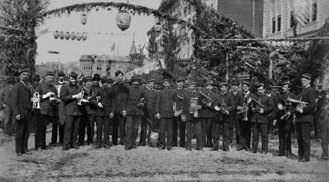 tHEN: An unidentified brass band poses at the intersection of Commercial Street (First Ave S.) and Main Street during the 1883 celebration for the completion of the transcontinental Northern Pacific Railroad.