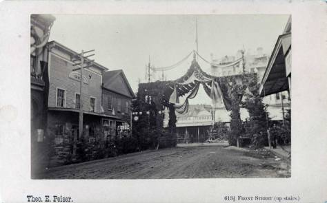 The Villard visit celebration arch erected at the head of Commercial Street where it originates at Mill Street, (Yesler Way). The view looks north from mid-block between Mill and Washington. Photo by Peiser. Courtesy MOHAI.