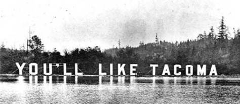 "The grandest of the ""You'll Like Tacoma"" signs was set along the north shore of Portage Bay for ready inspection from the AYPE grounds on the UW campus. Illuminated, its greatest effect was at night."
